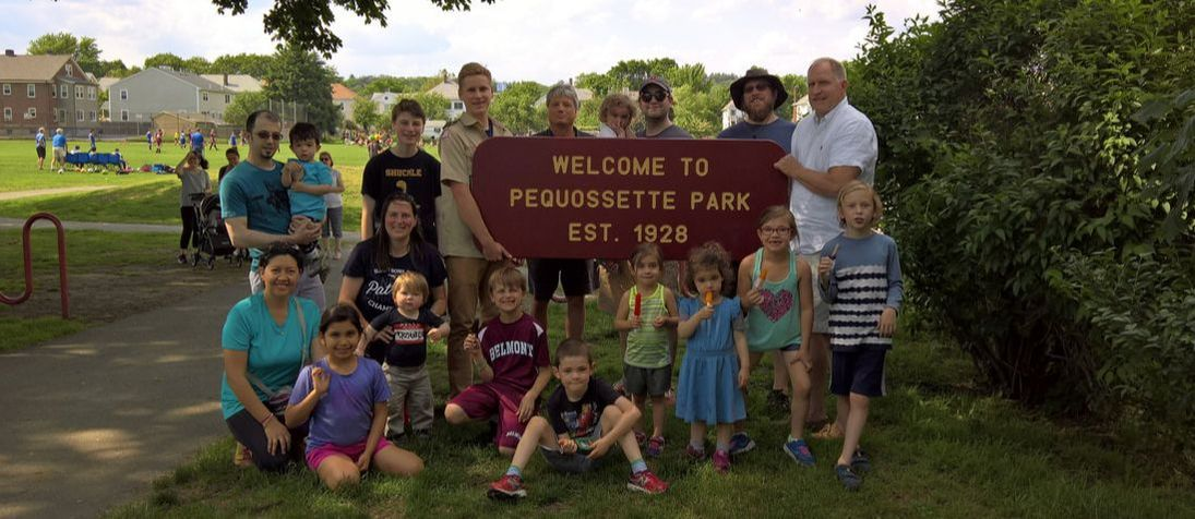 Volunteers hold the PQ Park sign at a spring gathering 2017.